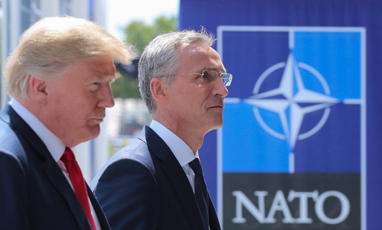 US President Donald Trump (L) walks with NATO Secretary General Jens Stoltenberg as he arrives to attend the NATO (North Atlantic Treaty Organization) summit, in Brussels, on July 11, 2018.